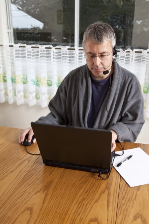 teleconference: Businessman working from home in pajamas (WINTER)  Stock Photo