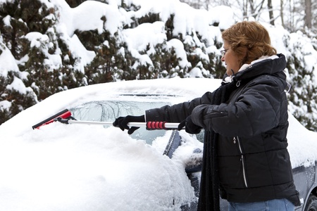 Woman removing snow from car windshield Stock Photo - 11677142