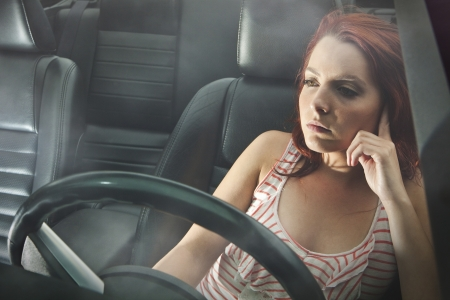 pensive young woman behind the wheel  photo
