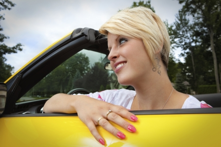 Happy young woman in a convertible car  photo