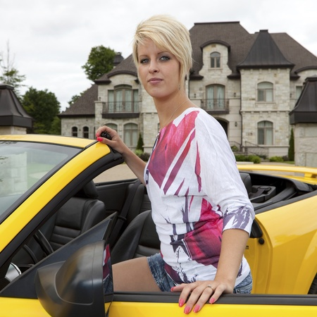 Wealthy young woman getting into a convertible car  photo
