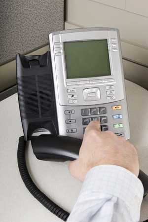 conference call: Office worker placing a call on an IP phone