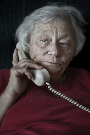 adult 80s: Pensive senior woman talking on the phone