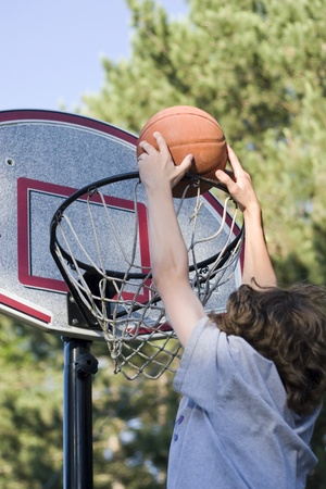 outside shooting: Boy playing basketball