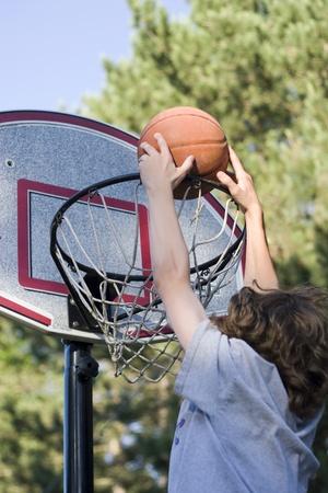 outside shooting: Boy playing basketball