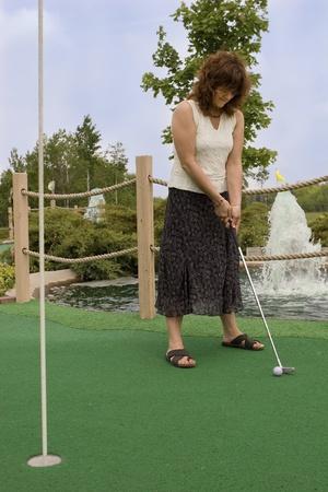 Woman enjoying a round of mini golf  photo