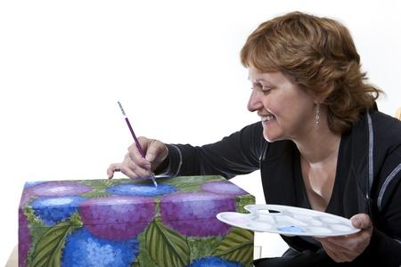 Vrouw Tole het schilderen van een houten kist Stockfoto