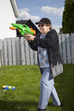 woman squirt: Senior woman in a water gun fight  Stock Photo