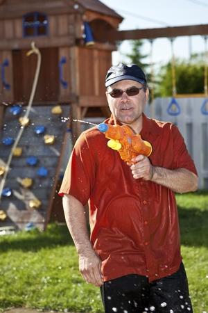 horseplay: Mature man in a water gun fight