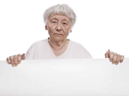 Serious senior woman holding a blank sign  스톡 콘텐츠