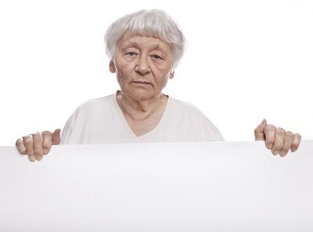 sad old woman: Serious senior woman holding a blank sign  Stock Photo