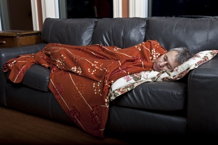guest house: Man sleeping on couch  Stock Photo