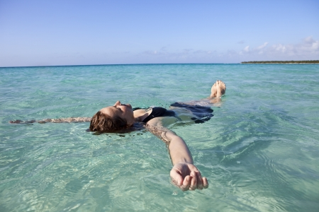 float: Woman floating and relaxing in the sea  Stock Photo
