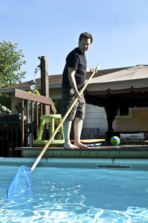 pool deck: Man cleaning his above ground swimming pool