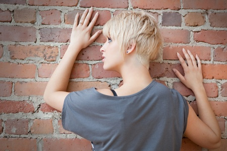 Beautiful blond against brick wall portrait  photo