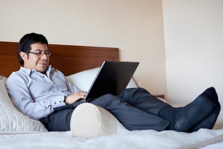 travelling salesman: Hispanic businessman using laptop in his hotel room