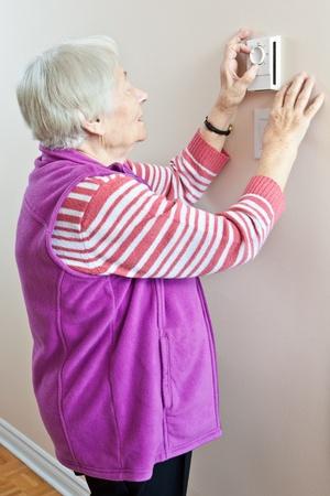 年配の女性が彼女のサーモスタットを調整します。