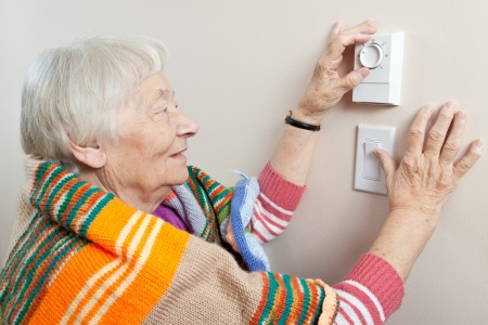 house coats: Senior woman adjusting her thermostat  Stock Photo