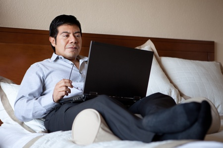 Hispanic businessman using laptop in his hotel room  photo