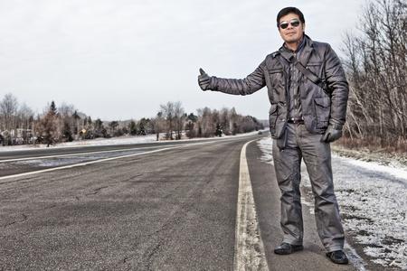 travelling salesman: Hispanic man hitchhiking in Canada during winter