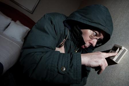 blackout: Invriezen man aanpassen thermostaat Stockfoto