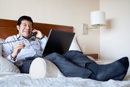 travelling salesman: Hispanic businessman on the phone and using laptop in his hotel room