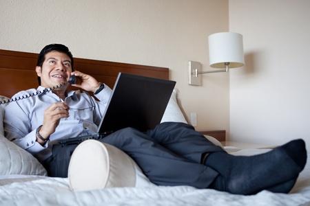 그의 호텔 방에서 전화와 노트북을 사용하는 히스패닉 사업가