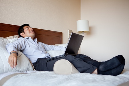 tired businessman: Hispanic businessman resting in his hotel room  Stock Photo