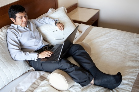 Serious hispanic businessman using laptop in his hotel room  photo