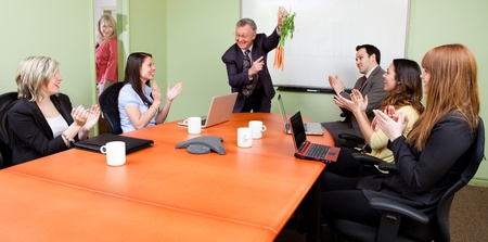 motivator: The great motivator dangling carrots and Business team motivated by positive presenter, Clapping employees