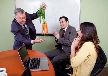 El gran motivador colgando las zanahorias y el equipo de negocios motivados por el presentador de positivo, aplaudiendo los empleados Foto de archivo