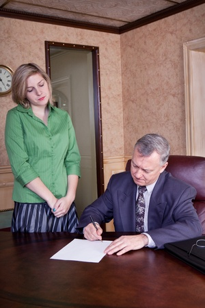 Admin getting signature from her boss Stock Photo - 12408567