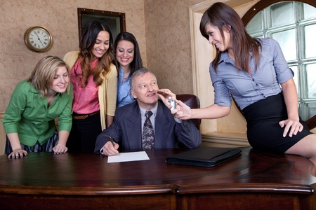 Senior executive signing a big contract with team of young women  photo
