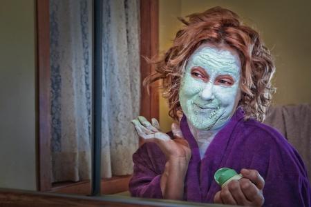 Donna narcisistica guardando nello specchio mentre si applica crema di bellezza Archivio Fotografico - 12408576