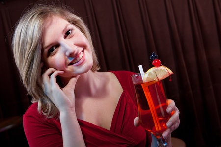 Attractive young woman with a drink at a nightclub Stock Photo - 13070227