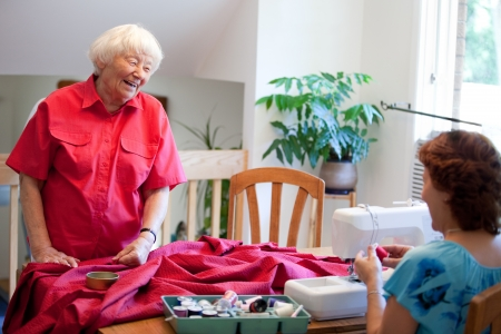 Volunteer helping senior with sewing project  photo