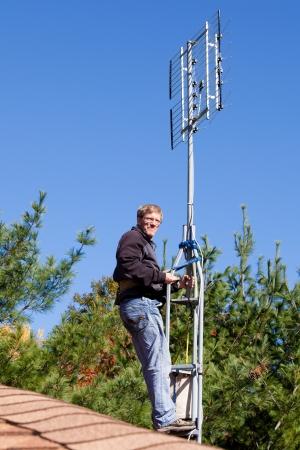 hdtv: Workman installing HDTV digital antenna on a house  Stock Photo