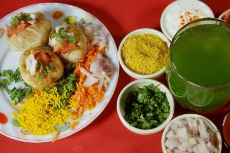 pani:  Close-up of puri and other ingredients of chaat