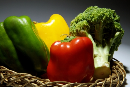 Bell peppers and broccoli in a wicker basket Stock Photo - 17327302