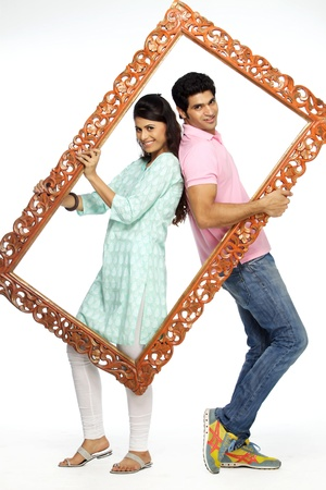 Portrait of a happy couple holding a frame