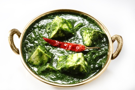 Palak paneer garnished with red chili