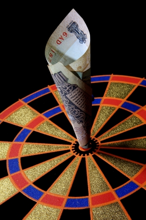 Close-up of a dart board with currency note on it photo