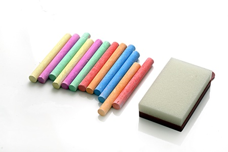 Chalks and duster arranged on white background