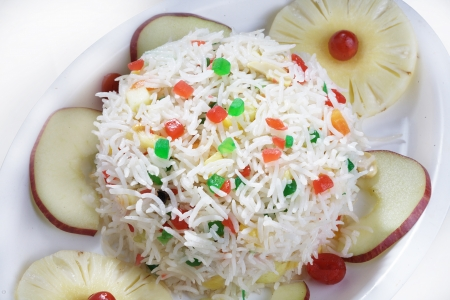 Fruit rice garnished with fruits and served in a plate photo