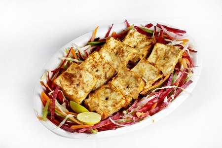 paneer: Paneer tikka garnished and served in a plate