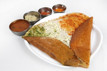 Dosa with chutney and sambar served in a plate