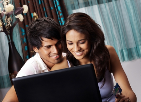 Couple shopping online on a laptop photo