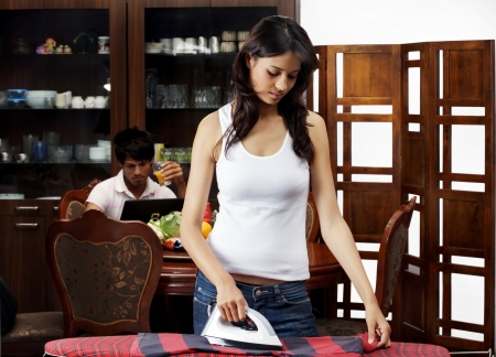Young woman ironing clothes with man having juice in the background