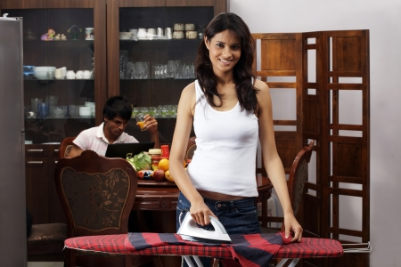Young woman ironing clothes with man having juice in the background photo