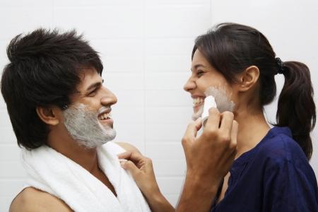 Man applying shaving cream on woman's face